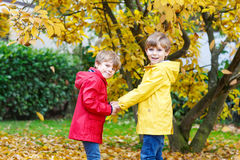 Two little best friends and kids boys autumn park in colorful clothes. Happy siblings children having fun in red and yellow rain coat and rubber boots. Family Stock Photography