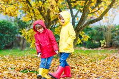 Two little best friends and kids boys autumn park in colorful clothes. Happy siblings children having fun in red and yellow rain coat and rubber boots. Family Royalty Free Stock Photography