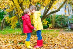 Two little best friends and kids boys autumn park in colorful clothes. Happy siblings children having fun in red and yellow rain coat and rubber boots. Family Stock Images
