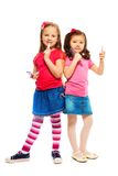 Two little big girls. Two girls Caucasian and Asian playing to be big like older sisters brushing and making up face, isolated on white, full length portrait Royalty Free Stock Images