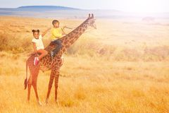 Two little black kids ride a giraffe in Africa. Two little black kids boy and girl ride a giraffe in Africa - mixed media royalty free stock photos