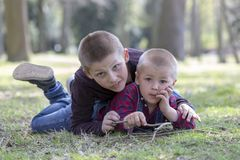 Two little blond brothers laying in grass in the spring.  royalty free stock images