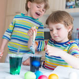 Two little blond kid boys coloring eggs for Easter Stock Photos