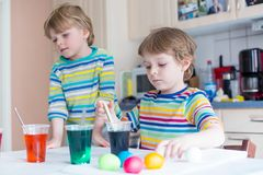 Two little blond kid boys coloring eggs for Easter holiday stock images