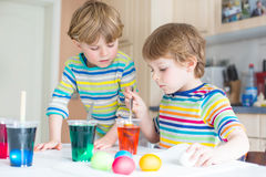 Two little blond kid boys coloring eggs for Easter Royalty Free Stock Images