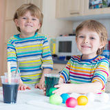 Two little blond kid boys coloring eggs for Easter Stock Photo