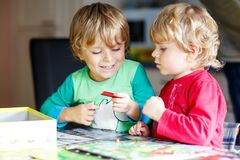 Two little blond kid boys playing together board game at home. Funny siblings having fun. Twins and best friends, toddlers learning interact, win and lose stock image