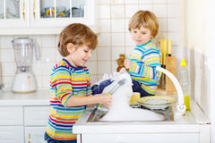 Two little blond kid boys washing dishes in domestic kitchen Stock Images