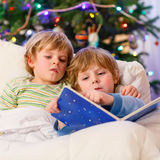 Two little blond sibling boys reading a book on Christmas. Two little blond sibling boys reading a book in bed near Christmas tree with lights and illumination Stock Photography