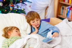 Two little blond sibling boys reading a book on Christmas. Two little blond sibling boys reading a book in bed near Christmas tree with lights and illumination Royalty Free Stock Image