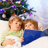 Two little blond sibling boys reading a book on Christmas. Two little blond sibling boys reading a book in bed near Christmas tree with lights and illumination Stock Images