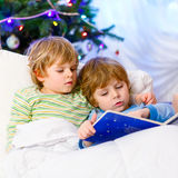 Two little blond sibling boys reading a book on Christmas. Two little blond sibling boys reading a book in bed near Christmas tree with lights and illumination Stock Image
