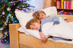 Two little blond sibling boys sleeping in bed on Christmas Stock Photo