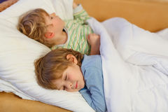 Two little blond sibling boys sleeping in bed Stock Photos