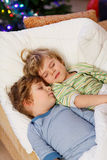 Two little blond twins boys sleeping in bed on Christmas Stock Photo