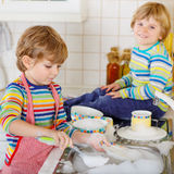 Two little blond twins boys washing dishes in domestic kitchen Stock Photo