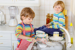 Two little blond twins boys washing dishes in domestic kitchen Stock Photos
