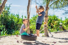 Free Two Little Blonde Boys Having Fun On The Swing On The Tropical Sandy Coast Royalty Free Stock Photo - 136476745
