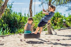 Free Two Little Blonde Boys Having Fun On The Swing On The Tropical Sandy Coast Stock Photography - 136628232
