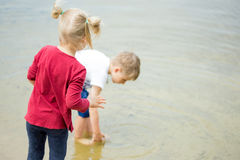 Two little blonde kids, boy and girl, stand on a shore of lake . Royalty Free Stock Photo