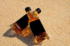 Two little bottles whiskey lie on the sand. Alcohol top view from above royalty free stock photography