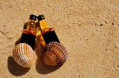 Two little bottles whiskey lie on the sand. Alcohol top view from above.  stock photos