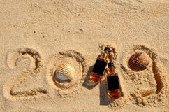 Two little bottles whiskey lie on the sand. New Year luxury alcoholic party, top view from above royalty free stock photos