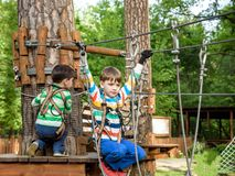 Two little boy boys kid in a helmet and with a safety carbine goes on a rope on the background of forest and sky. Healthy games stock images