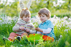 Two little boy friends in Easter bunny ears during egg hunt Stock Images