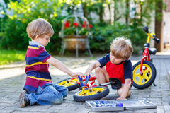 Two little boy friends, twins, learning to repair a bike and to to change a wheel. Siblings working together outdoors, on warm sunny day. Active leisure with Royalty Free Stock Photos