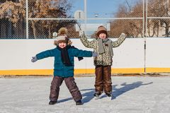 Two little boy on the ice rink in winter stock photography