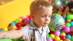 Two little boy playing in the dry pool with balls. Two cute little boys playing in the children`s entertainment center with plastic balls. Two little boy stock footage