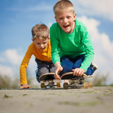Two little boy skating on the street in summer day Royalty Free Stock Image
