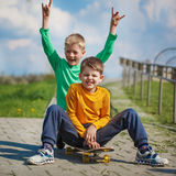 Two little boy skating on the street in summer day Stock Photos