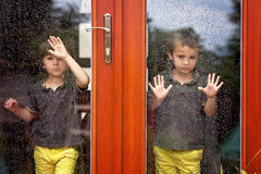 Two little boy, wearing same clothes looking through a big glass Royalty Free Stock Image