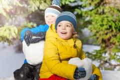 Two little boys with big snowballs in the forest Royalty Free Stock Image