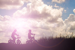 Two little boys bike silhouette Royalty Free Stock Image