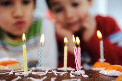 Two little boys blowing candles Stock Photos