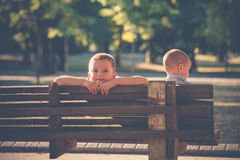 Two little boys brothers sit on wooden bench in park summer day Royalty Free Stock Photos