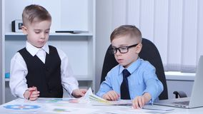 Two little boys businessman in the office consider graphs and charts stock video
