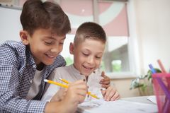 Two little boys drawing together at school royalty free stock images