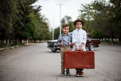 Two little boys dressed in vintage clothes are walking with a retro suitcase.  royalty free stock photography