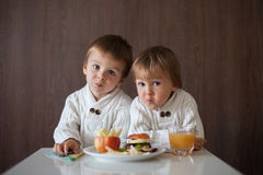 Two little boys, eating fruit sanwich Stock Image