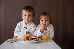 Two little boys, eating fruit sanwich Royalty Free Stock Image