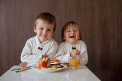 Two little boys, eating fruit sanwich Stock Photo