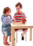 Two little boys eating strawberries at the table Stock Images
