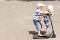 Two little boys enjoying a scooter ride stock images