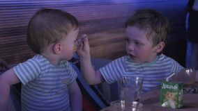 Two little boys feeding each other in restaurant. Children event. Celebration. Family stock footage