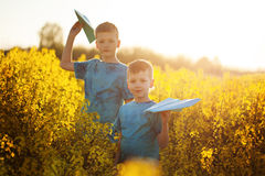 Two little boys friends with blue paper plane in summer yellow field. Brother love. Concept friendship. Two little boys friends with blue paper plane in summer Stock Photos
