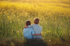 Two little boys friends holding around the shoulders in sunny summer day. Brother love. Concept friendship. Rear view. Two little boys friends holding around stock photos